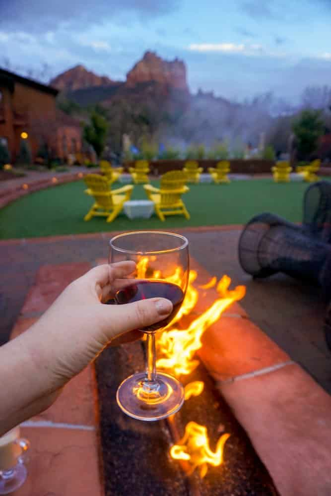 Kara of Whimsy Soul enjoys a glass of wine in Sedona Arizona in her Airbnb next to a fire and Red Rocks