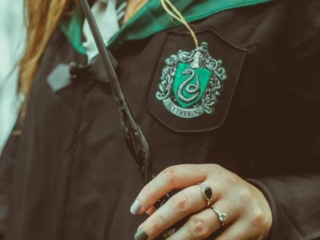Kara holding her wand donning her Slytherin robes
