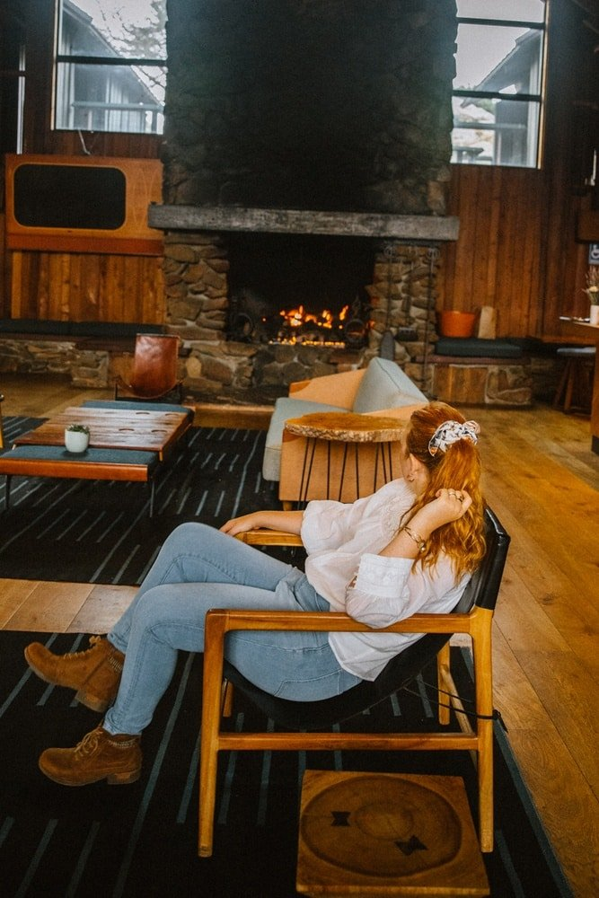 California travel blogger Kara Harms sits in the lobby of Timber Cove Resort wearing a white shirt and jeans